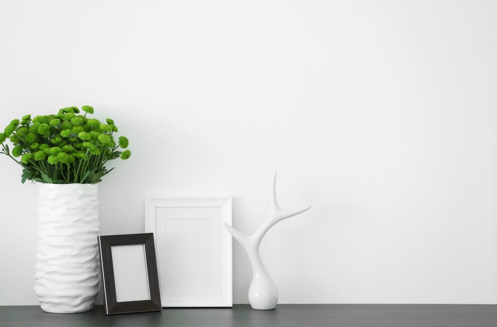 green chrysanthemum on top of table decorated with photo frame mockups and a white sculpture