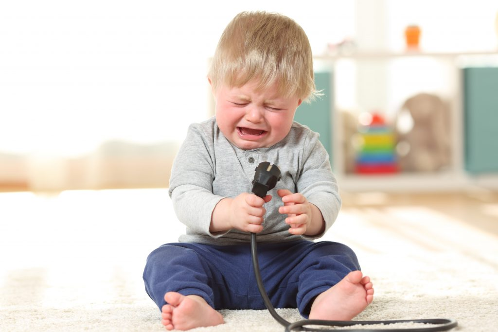 Baby crying holding an an electric plug